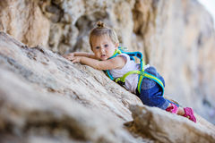 Little girl climbing up cliff Stock Image