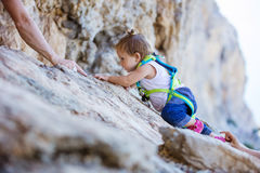 Little girl climbing up cliff Stock Photography