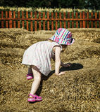 Little girl is climbing up on the haystack Royalty Free Stock Image