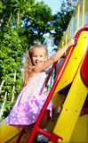 Little girl is climbing up on ladder in playground equipment Stock Photography
