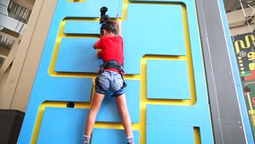 Little girl climbing a wall indoor. Courage little girl climbing a wall indoor while wearing a safety rope to train her strength, endurance and agility stock video