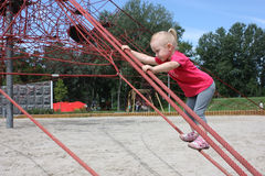 Little girl climbing through the web of ropes Stock Photo