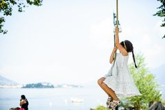 Little girl climbs on a big rope in the outdoor Stock Images