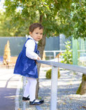 Little girl climbs on the railing at the zoo Stock Images
