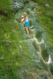 Little girl climbs rock Stock Images