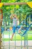 Little girl climbs on rope harness Stock Photos