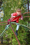 Little girl climbs and smiles on playground Stock Image