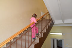 The little girl climbs up on a ladder handrail the second floor.  Royalty Free Stock Photo
