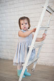 Little girl climbs up the stairs, a child, lifestyle, childhood, joy, family values, life style, the way development Royalty Free Stock Photo