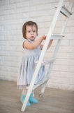 Little girl climbs up the stairs, a child, lifestyle, childhood, joy, family values, life style, the way development Royalty Free Stock Photography