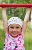 The little girl clings to crossbar Royalty Free Stock Photography