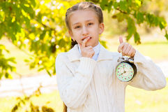 Little girl with a clock in his hands in the park Royalty Free Stock Image