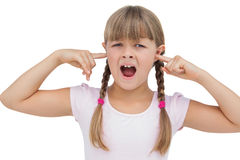 Little girl clogging her ears with her fingers. On white background Royalty Free Stock Image