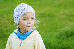 Little girl close up on green lawn. Beautiful little girl in yellow blouse close up on green lawn sheared Stock Photography