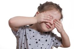 Little girl close your eyes with your hands. close-up stock photos