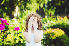 Little girl closed face with her hands, weeping, or playing hide Royalty Free Stock Image