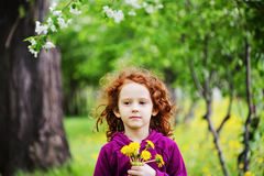 Little girl closed her eyes and breathes yellow dandelions in th Stock Photography