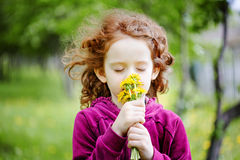 Little girl closed her eyes and breathes yellow dandelions in th Stock Photo