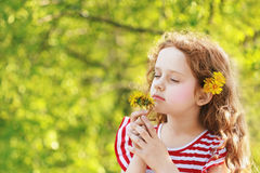 Little girl closed her eyes and breathes yellow dandelions in th Royalty Free Stock Photos