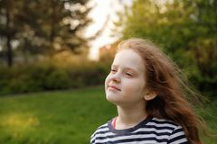 Little girl closed her eyes and breathing with fresh blowing air Stock Images