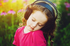 Little girl closed her eyes and listen to music on headphones in Stock Image