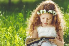 Little girl closed her eyes, praying, dreaming or reading a book royalty free stock image