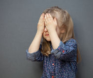 Little girl closed her face with her hands. Grey background Royalty Free Stock Photography