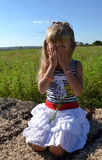 Little girl. The little girl closes her eyes with her hands Stock Photo