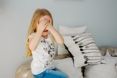 The little girl closes her eyes. Peekaboo. Children`s emotions stock images
