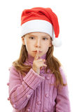 Little girl closeup in pink sweater. Beautiful little girl in pink sweater and red Christmas hat put finger to his lips, isolated on white background Stock Photo