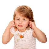 Little girl closing ears with fingers. Royalty Free Stock Photography