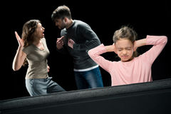 Little girl closing ears while parents quarreling Royalty Free Stock Photos
