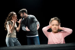 Little girl closing ears while parents quarreling. Family problems concept Stock Photography