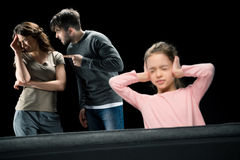 Little girl closing ears while parents quarreling,. Family problems concept Royalty Free Stock Photography