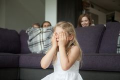 Little girl closing eyes playing hide and seek with family. Little girl closing eyes covering face with hands playing hide and seek game with parents and brother Stock Images