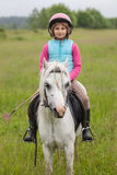 Little girl in the clothes for riding a horse sitting Sharpness on a horse  Outdoors Royalty Free Stock Image