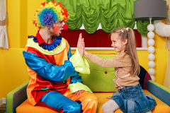 Little girl and  clown play palms. Royalty Free Stock Photography