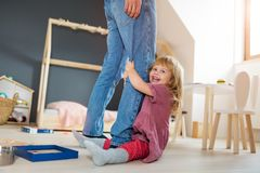 Little girl clutching father`s legs. And smiling stock images