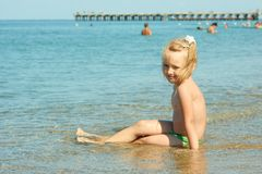 Little girl on the coastal seawater Stock Images