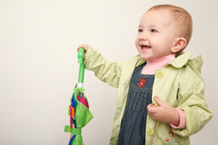 Little girl in coat with multicolor closed umbrell Stock Photo