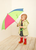 Little girl in coat with multicolor umbrella Stock Photos