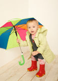 Little girl in coat with multicolor umbrella Royalty Free Stock Image