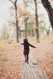 Little girl in a coat running away the road in the autumn park. stock image