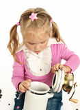 Little girl and a coffee grinder Stock Photos