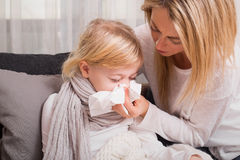 Little girl with cold and blowing her nose Stock Photography