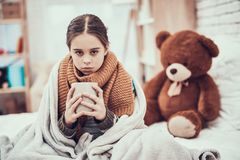 Little girl with cold in scarf and blanket with hot beverage in hands at home. Little girl with cold in scarf and blanket with hot beverage in hands near teddy royalty free stock images