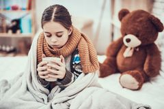 Little girl with cold in scarf and blanket with hot beverage in hands at home. stock image