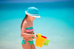 Little girl collecting seashells on white sand beach Royalty Free Stock Photography