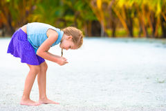 Little girl collecting seashells on white sand Royalty Free Stock Images