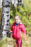 Little girl collects birch sap in woods Royalty Free Stock Image